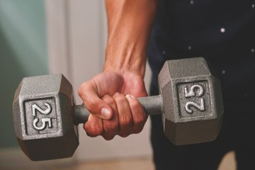 Man holding dumbbells while doing exercise