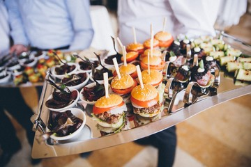 Waiters holding plate of snacks