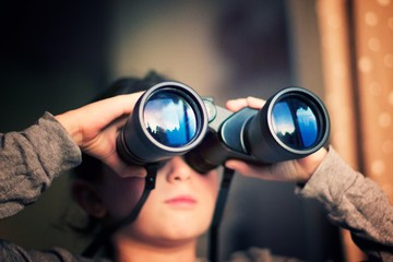Close up of a girl looking through the binoculars