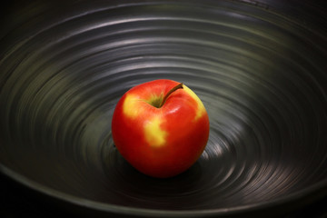 Apple on a plate./Bright apple, red with yellow spots, lies on a black ceramic plate.