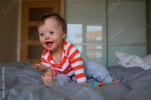 A cute baby boy with Down syndrome playing on the bed