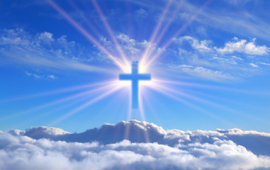 religious cross over cumulus clouds illuminated by the rays of holy radiance, concept