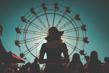 Rear view of a woman standing against ferris wheel