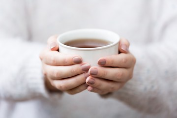 Close up of woman's hands holding cup of tea
