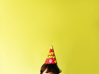 Girl wearing party hat against yellow background