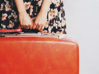 Close up woman's hand holding vintage suitcase