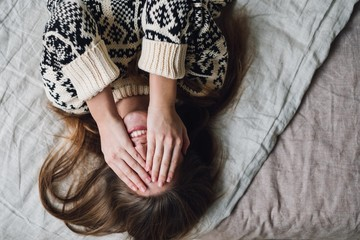 Woman covering her face with hands while lying on bed at home
