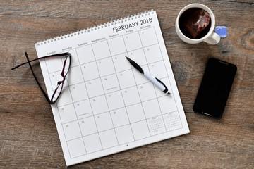 Overhead view of calendar, cell phone, pen, eye glasses and tea on desk
