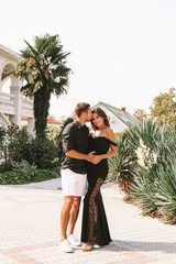 gorgeous pregnant woman with dark hair in elegant dress posing with her handsome husband