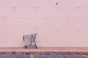 Shopping cart against pink wall