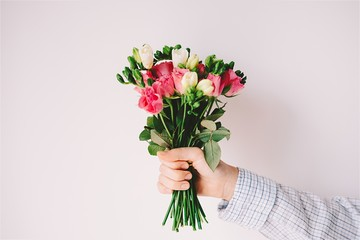 Close up of man's hand holding flower bouquet against white background