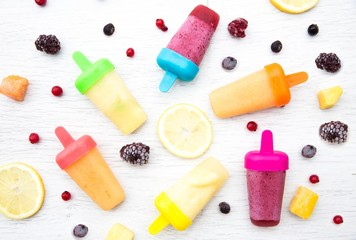 Colorful fruit smoothie ice lollipops on table surrounded by fruits