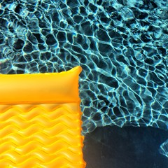 Inflatable bed floating in swimming pool