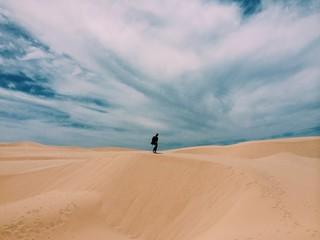 Man standing in desert landscape against cloudy sky