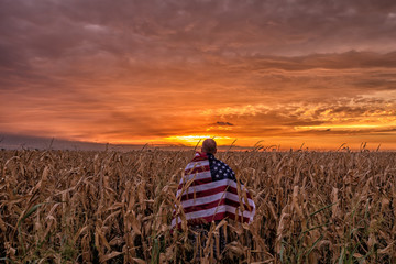 Man standing in corn field with American flag at sunset