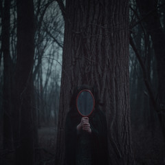 Woman standing with a mirror against tree in the forest