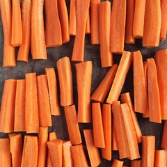 Close up of carrot slices on wooden cutting board