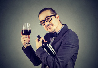 Happy man with glass of wine and bottle