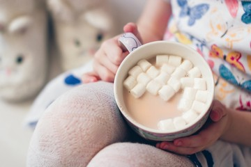 Mid section of girl holding a mug of cocoa with marshmallow