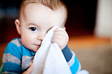 Portrait of a baby boy hiding face with blanket