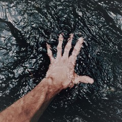 Close up of man's hand in water