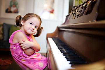 Portrait of little girl sitting at piano