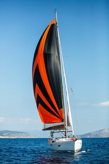 Magnificent luxury sailing yacht boat under colorful bright gennaker in the Aegean sea, Greece.