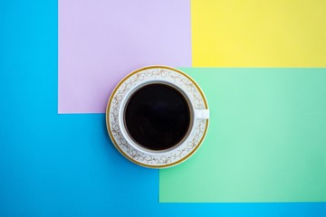 Overhead view of cup of coffee on colored background