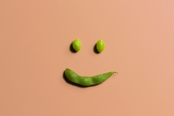 Smiley face made from soya bean on color background