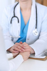 Medicine doctor hand reassuring her female patient closeup. Medicine, comforting  and trusting concept in health care