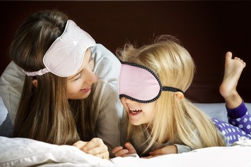 Smiling mother and daughter playing on bed