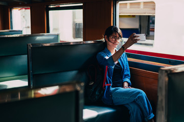 Asian woman traveler sits on train seat and used smart phone selfie photos while wait train leaving station of the railway station - travel and transportation concept