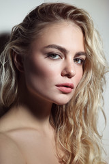 Fototapeta Portrait of young beautiful woman with blond curly messy hair