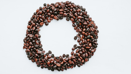 Coffee grains, beans in the shape of circle with free space inside on white isolated background, top view