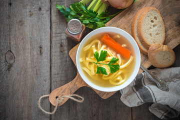 Chicken soup with noodles and carrot in white bowl.