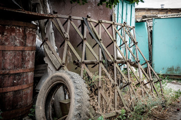 Vintage decorative old iron harrow near barn wall at countryside