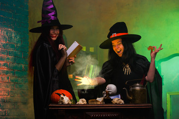 Portrait of two witches in black hats, potion