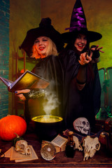 Image of smiling witches in black hats with book and magic cauldron at table with pumpkin and skulls