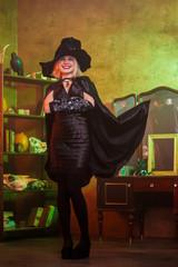 Portrait of witch in black hat, dress, developing cloak