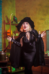 Image of screaming witch in black hat, dress on background of rack with pumpkin and crow