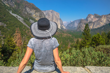 Traveler lifestyle woman with big hat contemplating Tunnel View overlook in Yosemite National Park. Relaxing at the popular El Capitan and Half Dome overlook. Travel holidays in California, Usa.