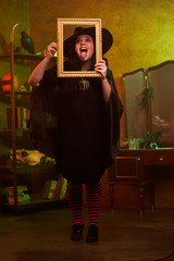 Full-length image of smiling witch with photo frame in hat