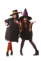 Full length image of two cheerful witches in hats and striped socks