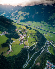 Aerial of houses and winding roads on mountains