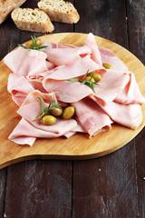 Sliced ham on wooden background. Fresh prosciutto. Pork ham sliced.