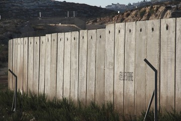 """A section of the concrete Israeli West Bank barrier wall, with the world """"Palestine"""" written on it, viewed from West Bank, Palestine"""