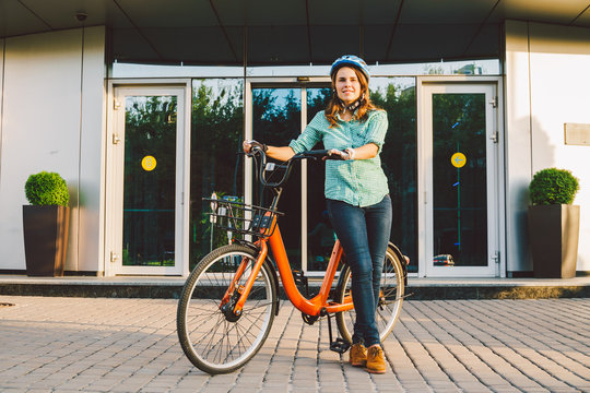 Theme to work on the bike. A young Caucasian woman arrived on environmentally friendly transport bike to the office. Girl in a bicycle parking office building in a helmet, gloves and shirt and jeans