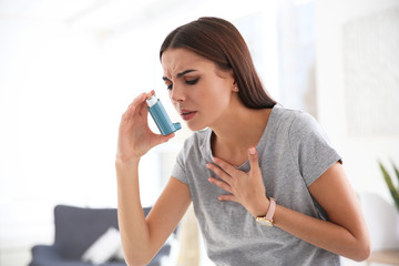Young woman with asthma inhaler in light room