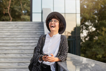 outdoor shot of stylish young woman, wears white shirt, summerhat and glasses laughs at joke, feels happy. Picture of young businesswoman check her social and laughs