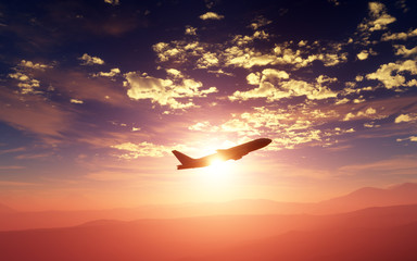 Big airliner flying at sunset or sunrise over a beatiful landscape of mountains. 3D illustration